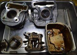 故障車の修理。分解されたシリンダーやキャブレター類