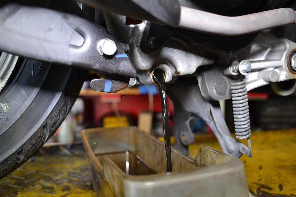 スクーターのドレンボルトを外し汚れたエンジンオイルを抜き取る