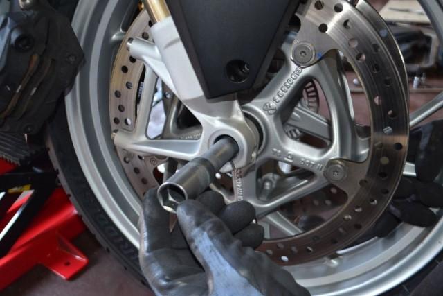 BMW R 1200 RT LC 両足でホイールの高さを調整しながらフロントアクスルシャフトを挿入します